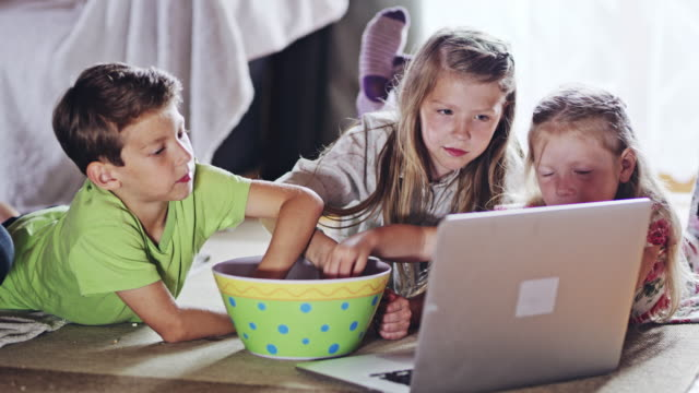 DS Three kids eating popcorn and watching a movie on a laptop