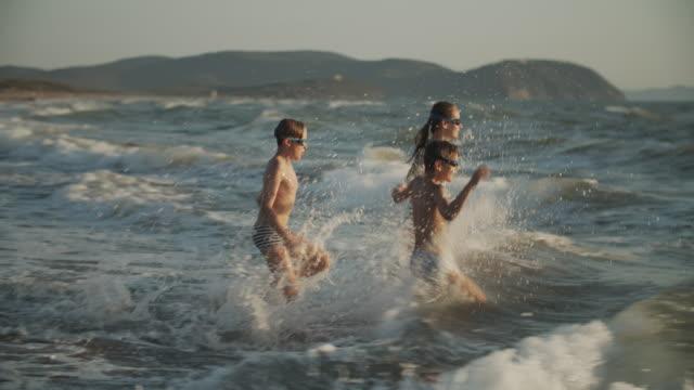 tre barn njuter av att springa vid havet - vanliga människor bildbanksvideor och videomaterial från bakom kulisserna