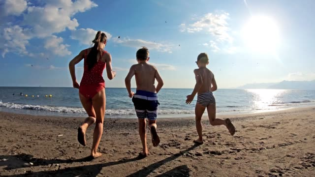three kids having fun running into sea - beach stock videos & royalty-free footage