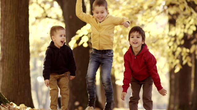 Tre bambini divertirsi con foglie autunnali