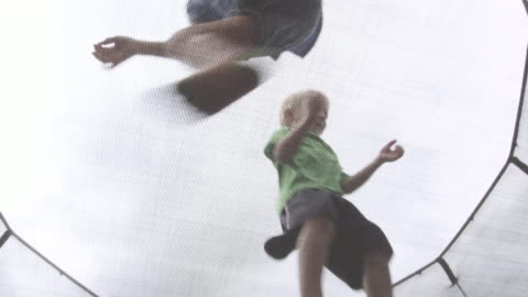 stockvideo's en b-roll-footage met three kids jumping on a trampoline, angle from underneith. - barefoot