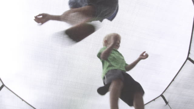 three kids jumping on a trampoline, angle from underneith. - barefoot stock videos & royalty-free footage