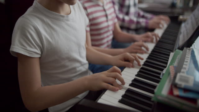three kids playing digital piano together - imgorthand stock videos & royalty-free footage