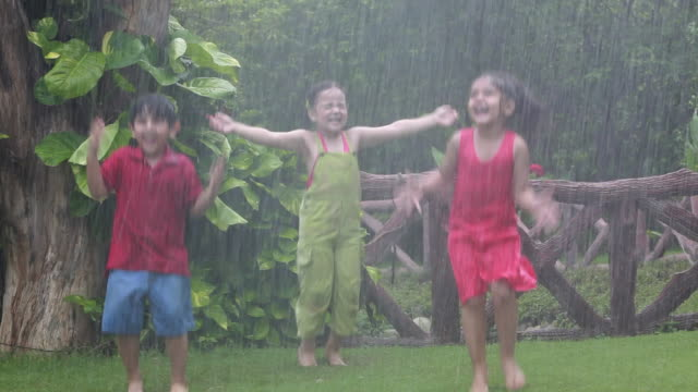 Three kids playing in rain