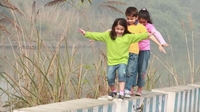 vídeos de stock, filmes e b-roll de three kids playing on the ledge  - cabelo preso