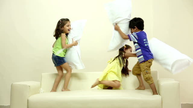 three kids playing pillow fight on the couch - 枕投げ点の映像素材/bロール