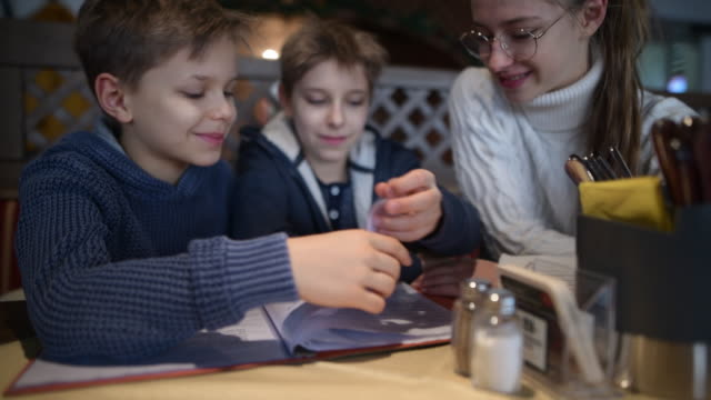 three kids reading menu at a restaurant - menu stock videos & royalty-free footage