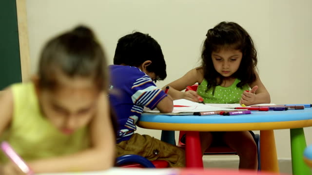 Three kids studying at school