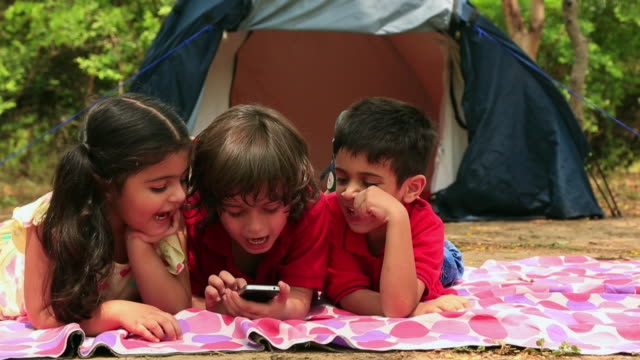 three kids using mobile phone in the forest - lying on front stock videos & royalty-free footage