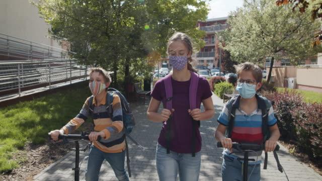 tre bambini che camminano a scuola durante la pandemia di covid-19 - person in education video stock e b–roll