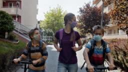 Three kids walking to school during COVID-19 pandemic