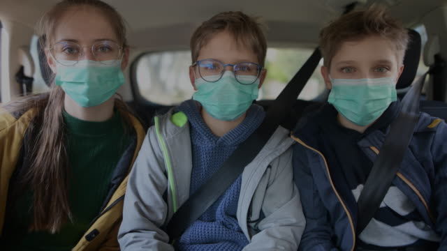 three kids wearing anti virus marks travelling by car - protective workwear stock videos & royalty-free footage