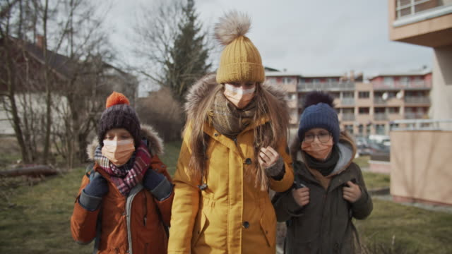three kids wearing anti virus masks going to school - air pollution stock videos & royalty-free footage