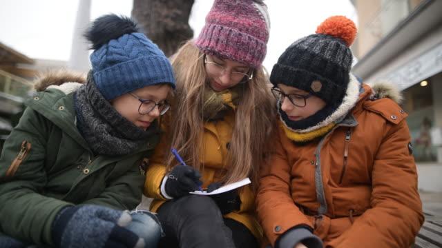 three kids writing postcards on street bench - imgorthand stock videos & royalty-free footage