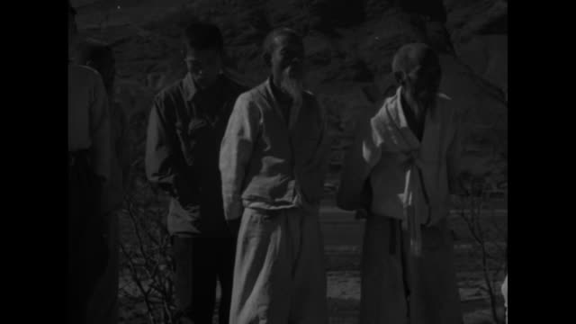 Three Korean men looking around / old woman children and men behind her / men and girl / refugees crossing field mountains in bg / closer view...