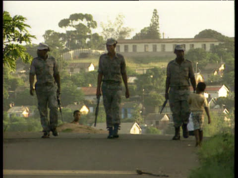 stockvideo's en b-roll-footage met three kwazulu police men with guns walk along road towards camera - 1992