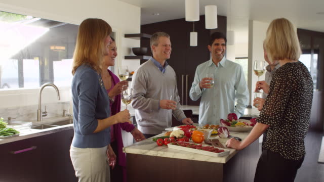 MS Three laughing couples standing together drinking wine in kitchen before dinner