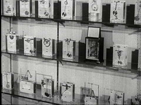 1943 ms three levels of shelves displaying various designs for clocks with clockwork exposed and pendulums rocking back and forth/ audio - three objects点の映像素材/bロール