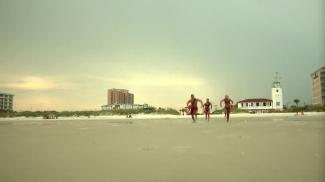 ws three lifeguards running on beach / jacksonville, florida, usa - bagnino video stock e b–roll