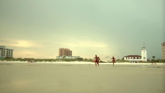 ws three lifeguards running towards sea / jacksonville, florida, usa - 男性と複数の女性点の映像素材/bロール