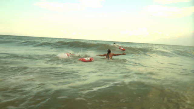 ws pov three lifeguards swimming to rescue man / jacksonville, florida, usa - bagnino video stock e b–roll