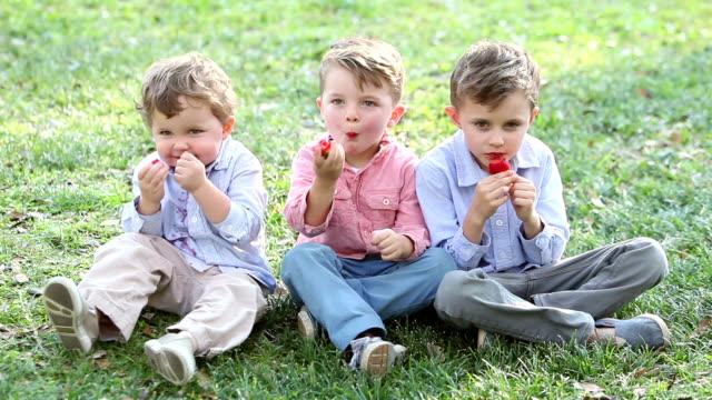 Three little boys eating strawberries