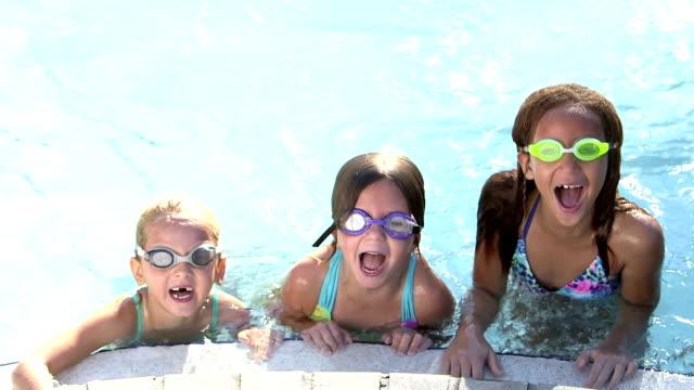 vídeos de stock, filmes e b-roll de três meninas nadam debaixo de água até a borda da piscina - prendendo a respiração