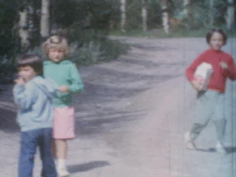 vidéos et rushes de three little girls walk along a dirt road and eat candy. - soeur