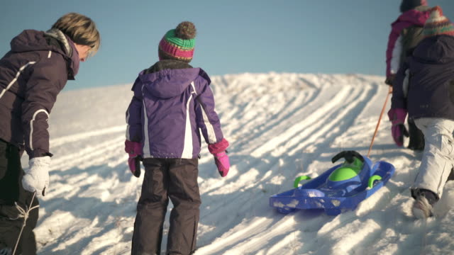 stockvideo's en b-roll-footage met three little girls with mother and bosbsleds on snowy hill - familie met drie kinderen