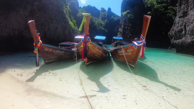 three longtail boats anchored on the beach in thailand - phi phi islands stock videos & royalty-free footage