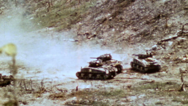 pan three m4 sherman tanks firing across blasted burned battlefield smoke drifting from target / iwo jima japan - schlacht um iwojima stock-videos und b-roll-filmmaterial