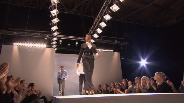ws three male and one female model, all wearing business wear, posing on catwalk in front of audience at fashion show/ london, england - ermafrodita video stock e b–roll