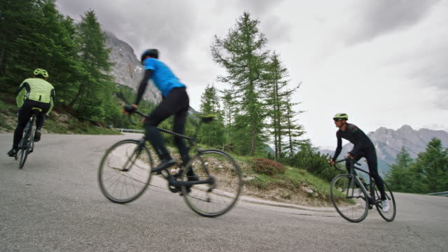 vidéos et rushes de trois cyclistes masculins jusqu'à la route haute dans les montagnes à cheval sur une journée nuageuse - origine ethnique