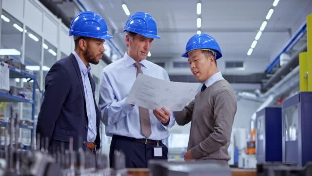 stockvideo's en b-roll-footage met ds drie mannelijke ingenieurs praten terwijl kijken naar de plannen staande in de fabriek - machine part