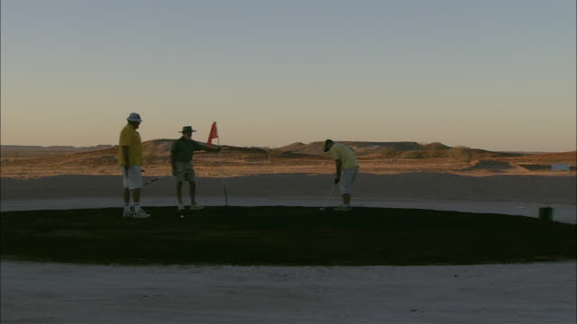 ws three male golfers on grassless golf course in desert landscapes at sunset, coober pedy, south australia, australia - coober pedy stock videos & royalty-free footage