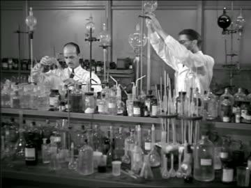 vídeos de stock, filmes e b-roll de b/w 1948? pan three male scientists working in laboratory amidst many glass bottles - artigos de vidro de laboratório