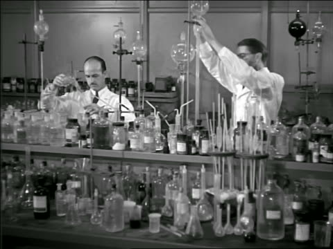 b/w 1948? pan three male scientists working in laboratory amidst many glass bottles - laboratory glassware stock videos & royalty-free footage