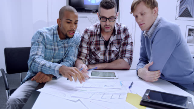 Three male startup colleagues checking the design plan