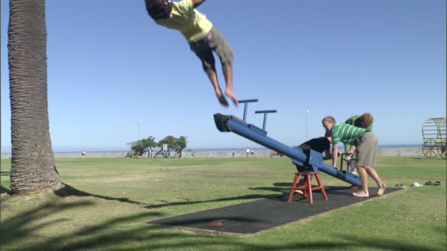 vídeos y material grabado en eventos de stock de ms three male students launching another male student off playground seesaw into air where he does back flip / cape town, western cape, south africa - balancín