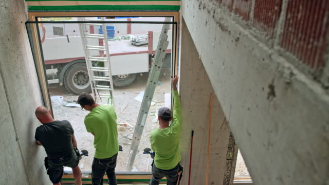 three male workers installing a large glass window into the opening - installing stock videos & royalty-free footage