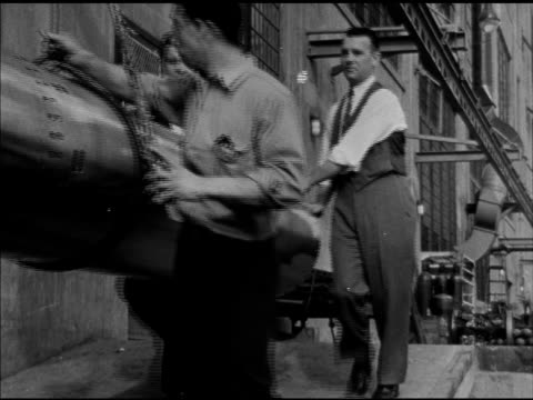 three males pushing hanging torpedo, workers working on torpedoes. vs large machine moving over factory production line, manager & officer going over... - torpedo stock videos & royalty-free footage