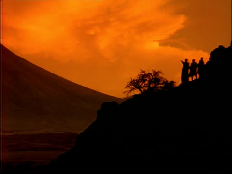 WA Three Masai standing on hill, pointing in to distance, silhouetted by red sky, Tanzania
