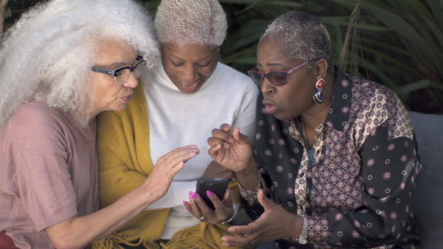 three mature woman in the garden looking intently at a mobile phone. - part of a series stock videos & royalty-free footage