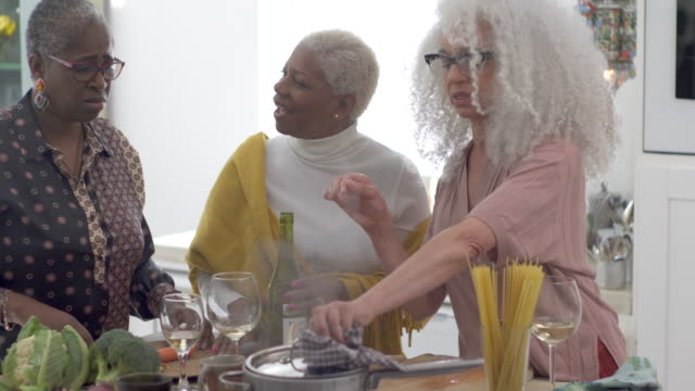 Three mature woman in the kitchen cooking and sharing a moment together.