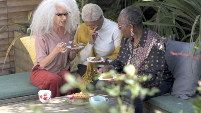 three mature woman sitting outside in the garden sharing and eating some cake together. - sister stock videos & royalty-free footage