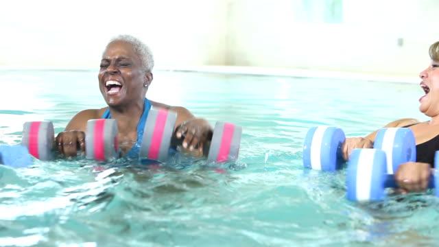 vídeos y material grabado en eventos de stock de tres mujeres maduras hablando, hacer aeróbicos en el agua - actividades y técnicas de relajación
