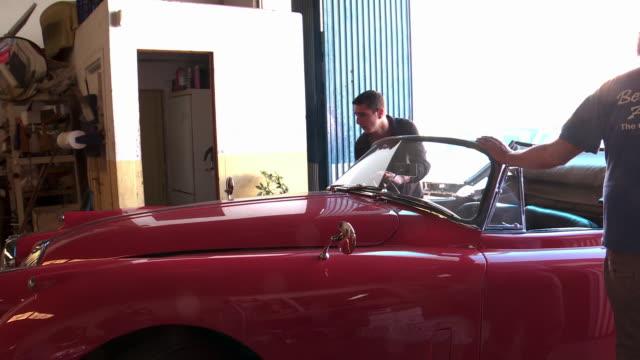three mechanics pushing a car. - repairing stock videos & royalty-free footage