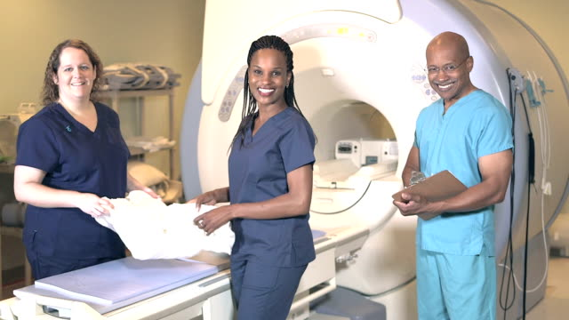 three medical professionals working in mri scanner room - mri scanner stock videos and b-roll footage