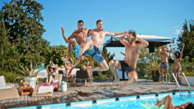 three men at a pool party jumping into the water together and making a big splash - shorts stock videos and b-roll footage