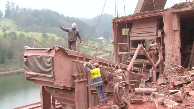 ms three men attaching chain with crushing machine at quarry / taben-rodt, rhineland-palatinate, germany - 石切場点の映像素材/bロール